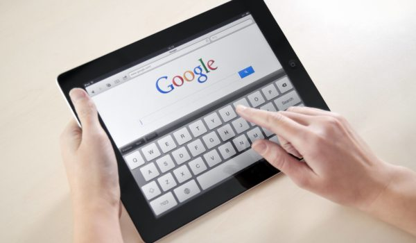 Person accessing Google search engine homepage on their tablet device