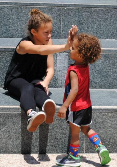 Two children high-fiving each other atop granite stairs