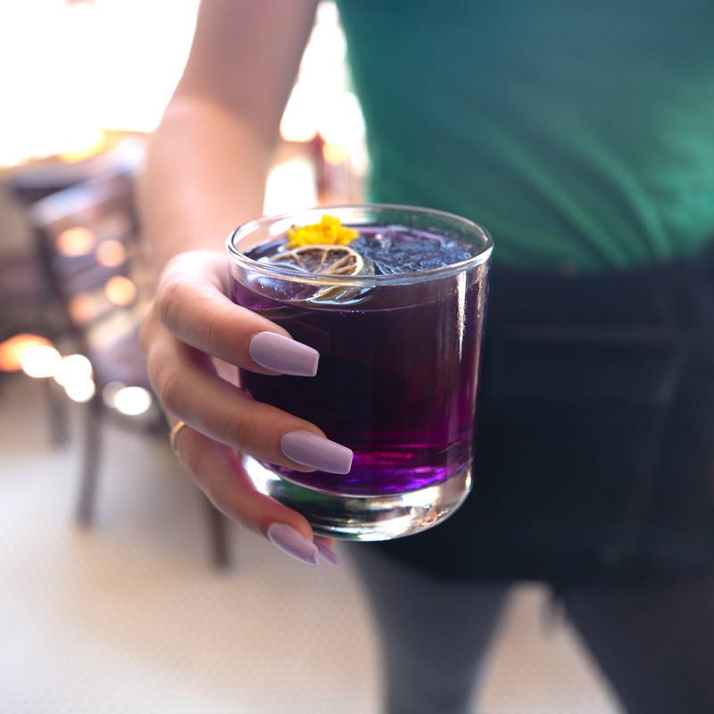 Young woman holding purple cocktail served at McNear's Saloon and Dining Hall