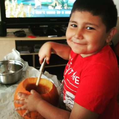 Young child carving pumpkin for Halloween