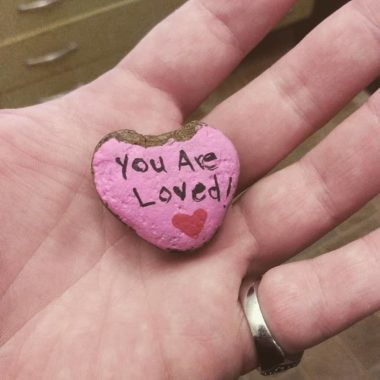 Person holding small heart shaped painted rock with