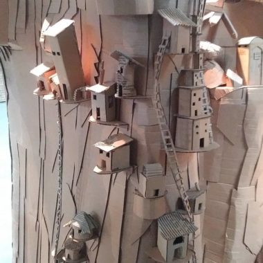 Cardboard sculpture of small houses built into cliffside